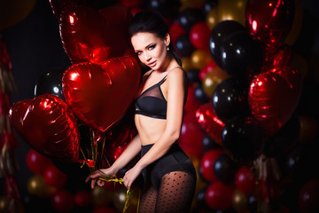 Perfect, sexy body and breast of young woman wearing seductive lingerie and black tights. Beautiful hot female in underwear posing in sensual way in St. Valentines day interior with balloons.