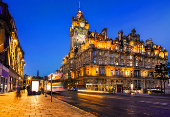 Streets of Edinburgh, Scotland, at night with light trails of street traffic on Princes Street.