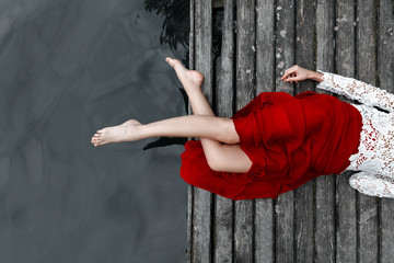 Legs of a girl in a red skirt on a bridge