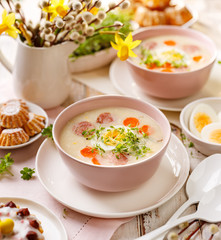 White borscht, polish Easter soup with the addition of white sausage and a hard boiled egg in a ceramic bowl. Traditional Easter dish in Poland
