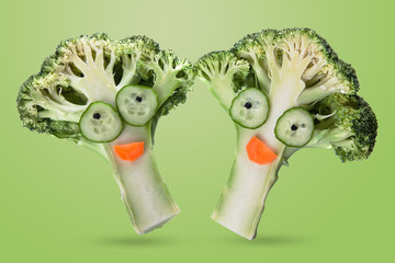 creative funny vegetables. Broccoli and cucumber on a light green background