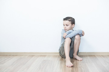 Sad boy sitting lonely in the room.Isolated on the white background