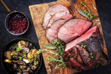 Photo Stands Ready meals Barbecue dry aged haunch of venison with mushroom and potatoes as close-up on an old cutting board