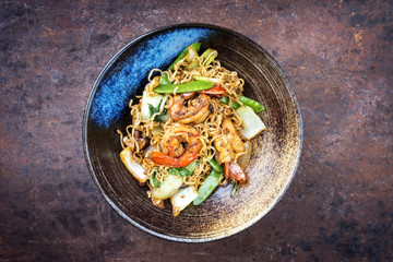 Traditional stir-fried Thai phat phak kung with mie noodlesas top view in a bowl with copy space