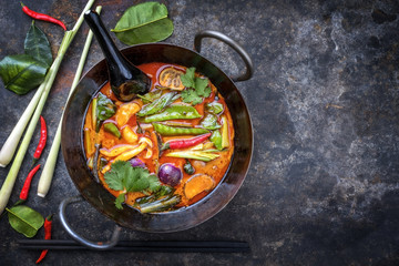 Traditional Thai kaeng phet red curry with vegetables as top view in a wok with copy space right