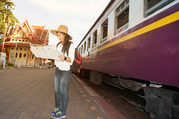 Pretty Asian traveler backpacker female looking map and waiting train at railway station in Thailand.