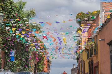 Colorful, festive flags, strung across colorful buildings, in San Miguel de Allende