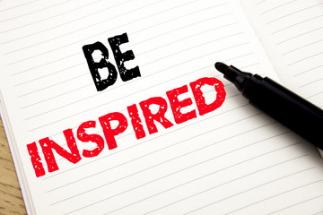 Be Inspired. Business concept for Inspiration and Motivation written on notebook with copy space on book background with marker pen