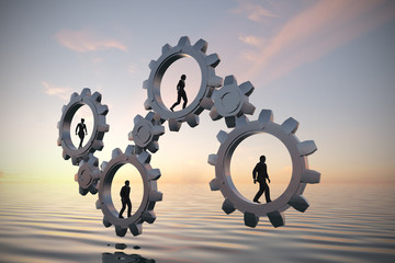 Gears of teamwork at sea at sunset. Executives walking inside gears at sea at sunset demonstrate the power of cooperation and synergy