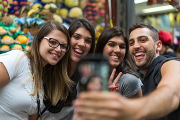 Friends taking a selfie with mobile in a Municipal Market, Sao Paulo, Brazil