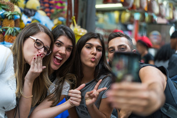 Friends taking a selfie with mobile in Food Market