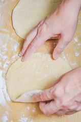 Woman doing manually the flat cake of leavened wheat dough