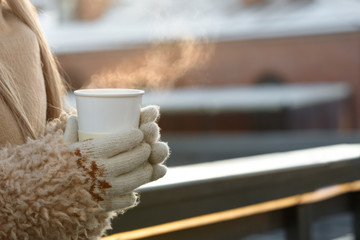 Female hands in white mittens holding steaming white cup of hot coffee or tea, outdoor/ Winter time concept/ Cup of hot coffee or tea in hands in cold winter sunny day, closeup/ Bask in the cold