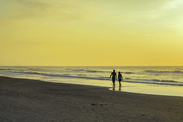 Woman and man walking o a beach at sunrise