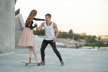 Ballerina on a skateboard. The guy helps