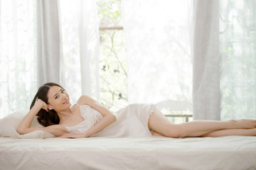 Young women lie on the bed