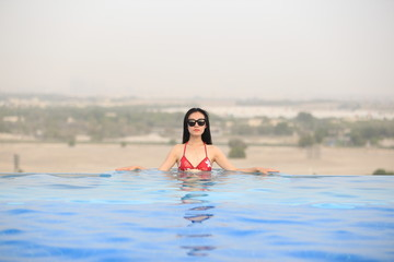 a woman in bikini in a swimming pool over desert in dubai, UAE