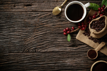 Top view mockup on wood background with a cup of coffee and red ripe coffee beans. Top view with copy space, flat lay.
