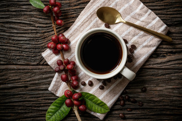 A cup of coffee on wooden desk with red ripe coffee beans.