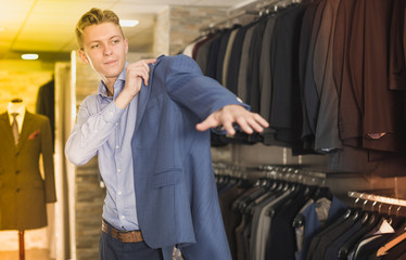 Man purchaser trying jacket in the dress shop