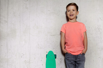 Cute little guy posing with skateboard against gray wall. Boy with skateboard outdoors standing near gray wall, copy space. Portrait of skater boy in pink T-shirt, concrete wall on background.