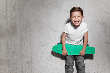 Attractive little boy with green skateboard in his hands. Smiling guy in white T-shirt standing near grunge concrete wall. Concept of activity and happy childhood.