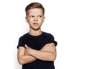 Portrait of little boy in black T-shirt unlike something, isolated on white. Studio portrait of guy crossed his arms over his chest. Emotion of discontent.