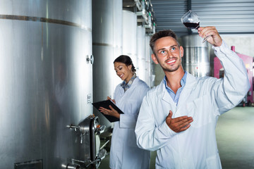 Man worker  standing with glass of wine in fermenting section on winery