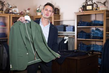 Smiling guy shopper choosing new jacket