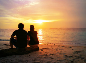 Back of loving couple sitting side by side on tropical beach with dramatic sunset or sunrise sky background. Happy young girlfriend and boyfriend in love on vacation. Valentines Day, loving concept.