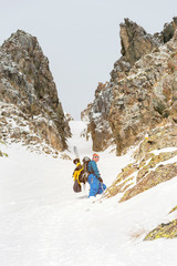 Extreme skiers climb to the top along the couloir between the rocks before the descent of the freeride backcountry
