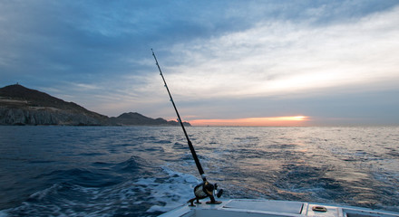 Sunrise view of fishing rod on charter fishing boat on the Pacific side of Cabo San Lucas in Baja Mexico BCS