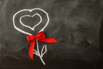 Valentine heart and red bow on the chalkboard
