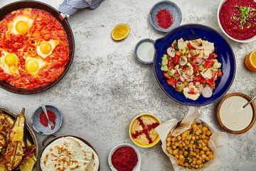 Overhead image of traditional jewish and middle eastern food: pita, fattoush, tabouli, shakshuka, balila, hummus and spicy beetroot dip. Text space.