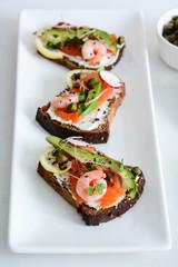 Smorrebrod, traditional Danish open sanwiches, dark rye bread with salmon, avocado, shrimp and micro-greenon a white plate.