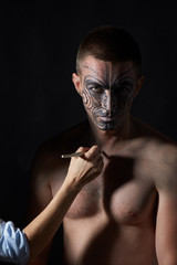 Portrait of a man with a tattoo on his face in the style of a Maori.