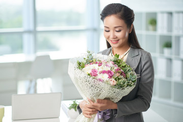 Happy business lady with flowers