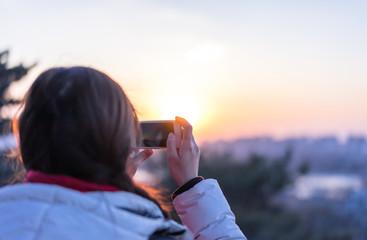 beautiful girl taking photo during sunset