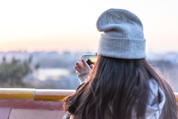 beautiful girl taking photo during sunset