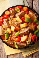 Philippine cuisine: kaldereta beef with vegetables close-up. Vertical top view