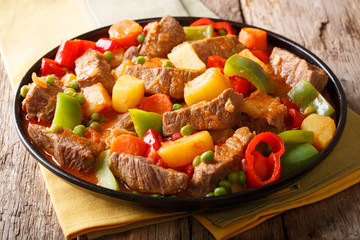 Beef filipino kaldereta with vegetables close-up on a plate on the table. horizontal
