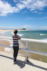 Woman looking at Nobbys Beach - Newcastle Australia. Newcastle is Australia's second oldest city and has many beautiful beaches