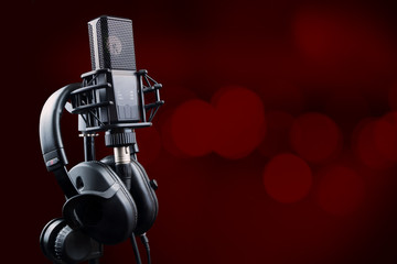 Professional microphone and headphones on red background