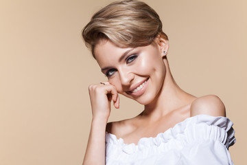 Young smiling woman with short blonde haircut. Portrait of beautiful model in white dress with bare shoulders. Portrait of cute girl with fresh make-up, isolated on beige background.