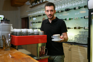 Men barista hold cup of coffee. Serving a client. Focus on beverage. Shallow depth of field.