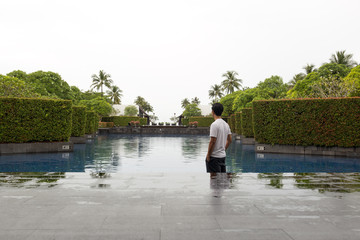 Man standing at swimming pool of luxury hotel