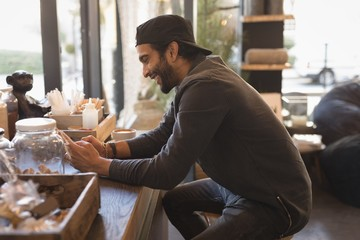 Man using mobile phone in coffee shop