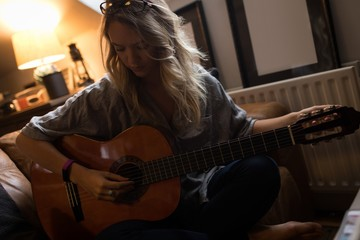 Young woman sitting and playing guitar