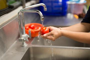 Woman hands washing fresh tomatoes under kitchen