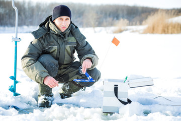 A young man is fishing from a hole on ice. Winter fishing